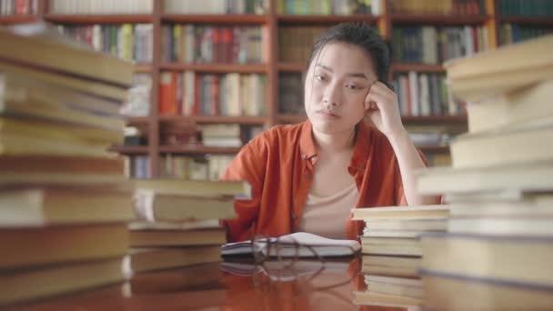 Rozrušený asijský studentka sedí za stohy knih, akademický tlak