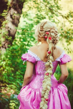 Girl with long luxuriant hair, braided in a braid,  beautiful hairdo, back in the woods.