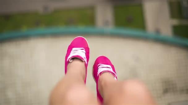 Ženské nohy v růžové tenisky, kyvné