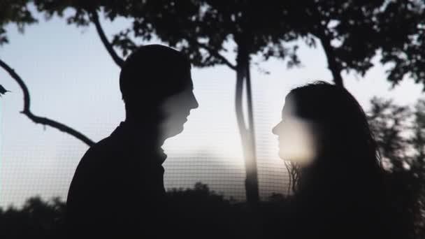 Silhouetten von jungen Paar küssen