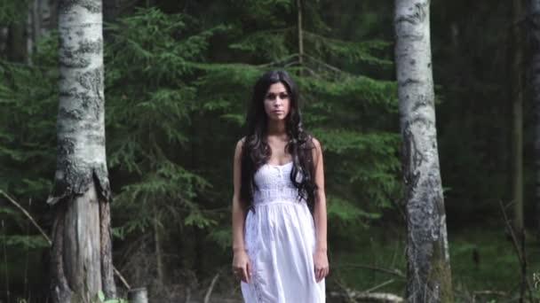 Mladá žena stojí v lese