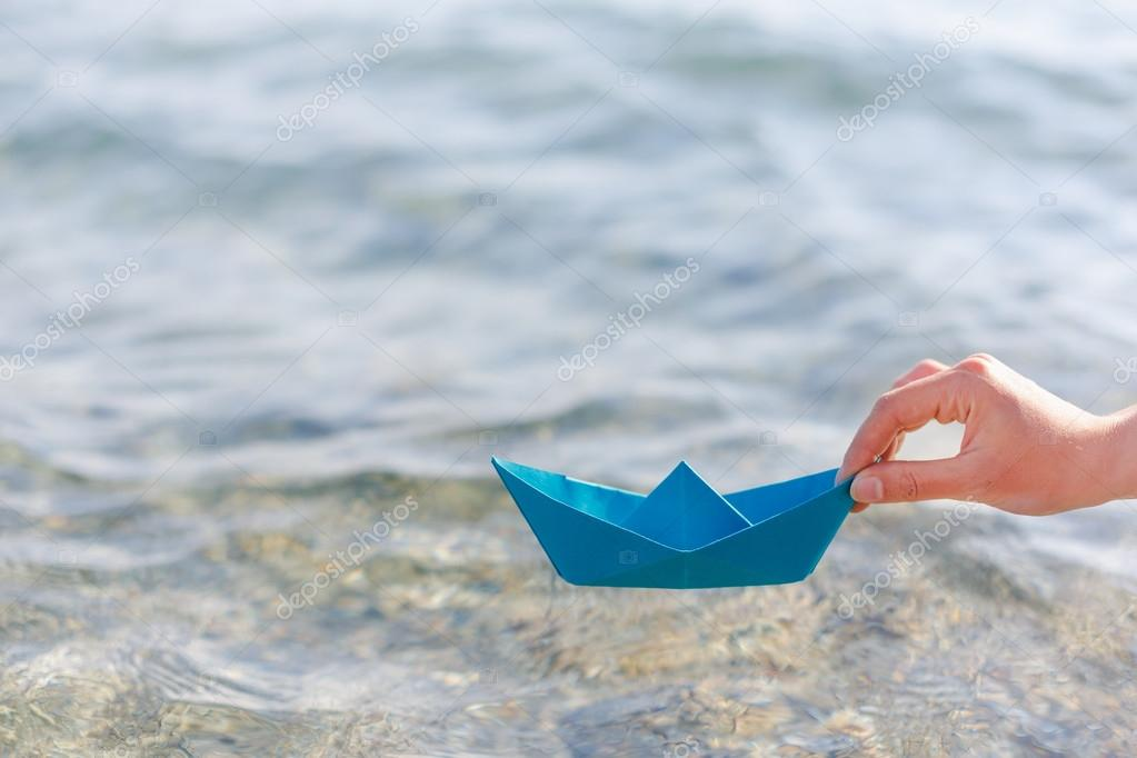 Female hand holding paper boat