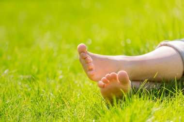 female bare feet on grass