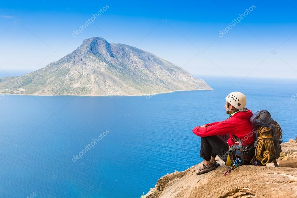 rock climber having rest sitting on the rock