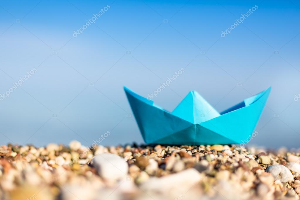 paper boat on pebble beach