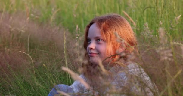 Cute beautiful teenager girl with long red hair sitting on the grass on summer field, enjoying the sun and adjusts her hair