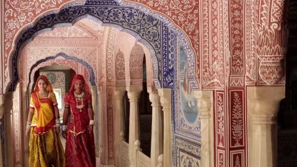 ladies wearing Saris in ornate passageway
