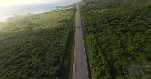 Cars drive on road along the Big Sur