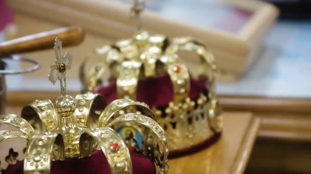 Close up of two gold wedding crowns