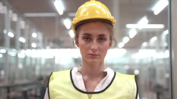Arbeiterinnen tragen Schutzmaske und Schutzhelm und tragen in einer sauberen Hightech-Fabrik grüne reflektierende Schutzanzüge. Konzept des intelligenten Industriearbeiters.