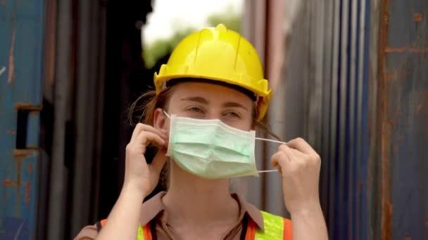 Arbeiterinnen ziehen Schutzmaske und Schutzhelm aus und tragen im Outdoor-Lager grüne reflektierende Schutzanzüge. Konzept der Sicherheitsbranche Arbeiter in Betrieb.