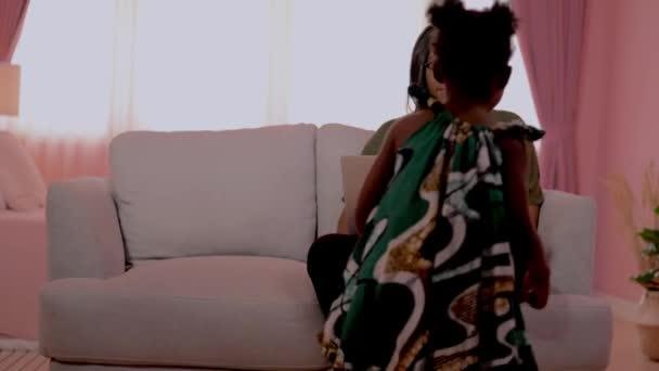 Konzeptmenschen arbeiten von zu Hause aus. Mutter arbeitet mit Laptop und sitzt im Sessel. Während Mädchen mit Mama sitzen und mit Mama spielen.
