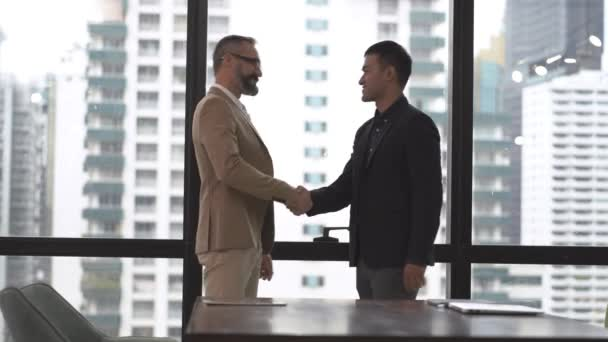 business senior man and asian man people shake hands at conference office room with glass wall  outdoor modern city skyline tower.