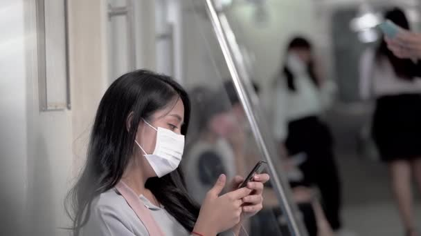 business woman with face mask using smartphone and sitting in metro train subway with people traveling in public transportation. Concept new normal life with Pandemic Flu Corona Virus.