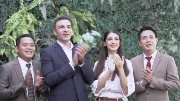 Portrét úspěšného obchodního týmu, který se dívá na kameru a tleská a tleská. Různorodí podnikatelé stojí společně na venkovní zelené zdi rostlin na pozadí.