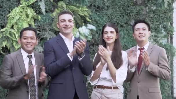 Portrait of successful executive business team looking at camera and clapping and applause by hand. Diverse business people standing together at outdoor green wall plant background.