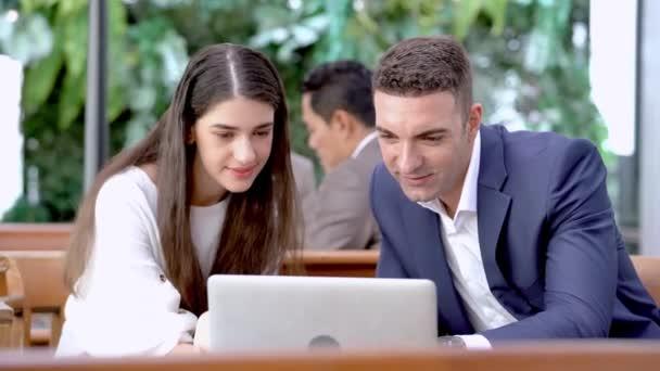 Geschäftsfrau und Mann schauen auf Computer-Laptop. Diverse Geschäftsleute arbeiten im Restaurant Outdoor zusammen.