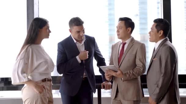Gruppe erfolgreicher Führungskräfte, die sich unterhalten und die Hand schütteln, um zu feiern. Diverse Geschäftsleute treffen sich im Outdoor-Wolkenkratzer.