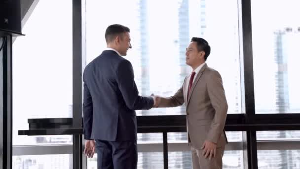 executive business team talking and shaking hand to celebrate. Diverse business people meeting together at outdoor skyscraper.