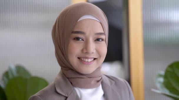 Porträt glücklicher Gesichter islamische Geschäftsfrau mit Kopftuch. Asiatin mit beigem Schal bedeckt. Frauengesicht hautnah in Empfangshalle willkommen.