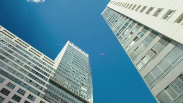 Time-lapse blue cloudy sky white glass buildings