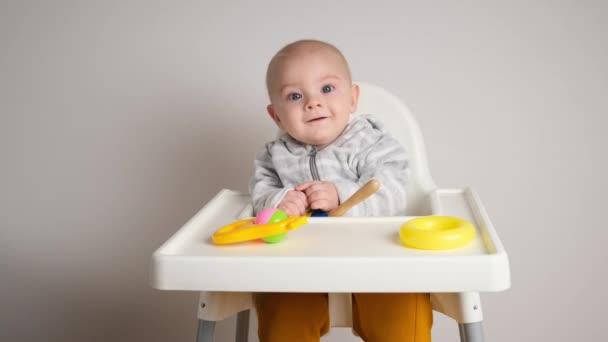 Egy kisfiú vigyorog a baba etetőszékében. Imádnivaló kisfiú műanyag játékokkal.