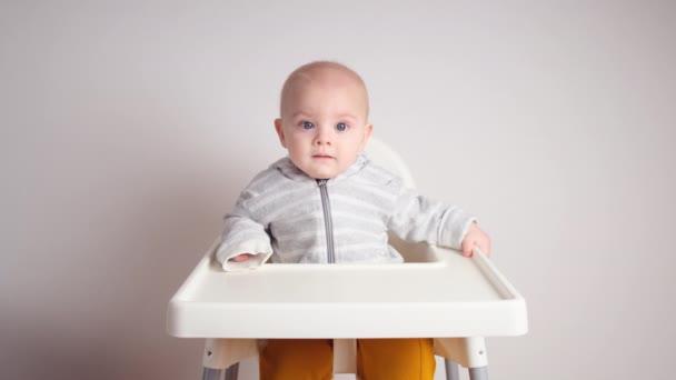 Boldog kisfiú ül a tolószékben. Imádnivaló 8 hónapos kaukázusi csecsemő kisfiú mosolygós.