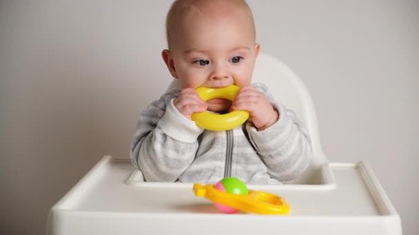 Koncept zoubkování. Kavkazský chlapeček sedí na vysoké židli a kouše plastovou hračku.