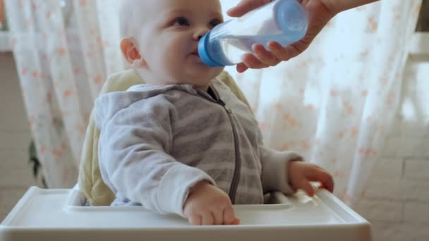 Mother gives her little son pure water from a bottle. Happy baby drinking fresh water in kitchen.