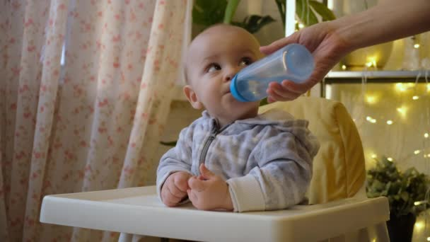 Mothers hand gives toddler pure water from a bottle at home. Small boy drinking fresh water in kitchen.