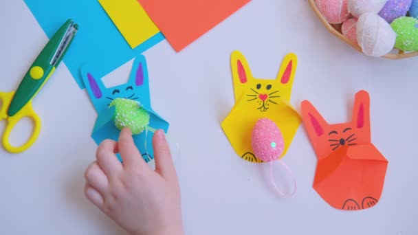 Childrens hands put an Easter egg of a paper bunny craft.