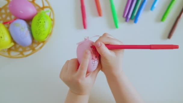 Childrens hands paint the Easter egg with red marker