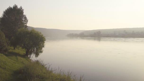 Široké hladké hluboká řeka teče pomalu ve velkém údolí v ranní mlze