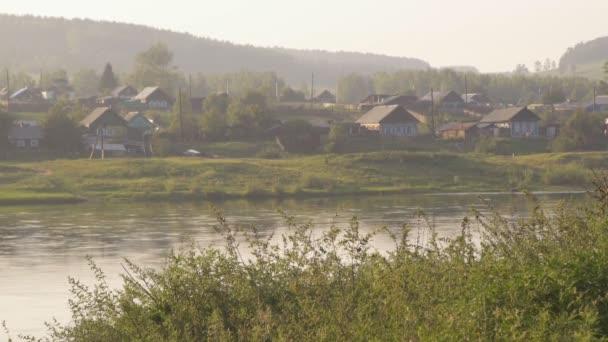 Ruské dřevěné vesnice na břehu řeky v ranním slunci