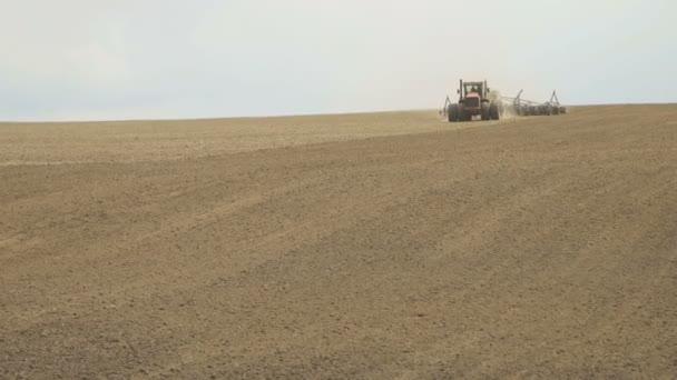 Traktor prasnice zoraného pole pomocí secí stroje.