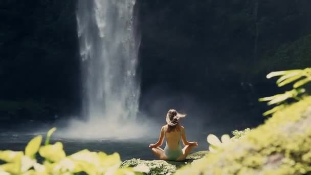 girl meditating in front of waterfall