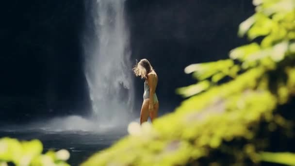 girl in front of a waterfall with a leaf