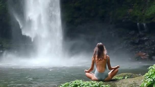 Mädchen vor Wasserfall zu meditieren