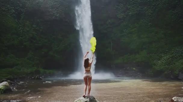 dívka před vodopádem s listem