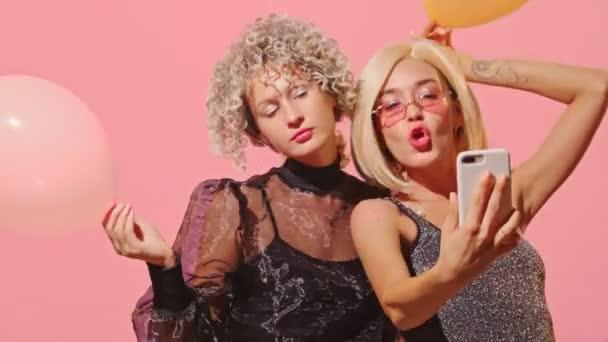 Fiatal, gyönyörű, divatos nők együtt csinálnak szelfit a rózsaszín falon..