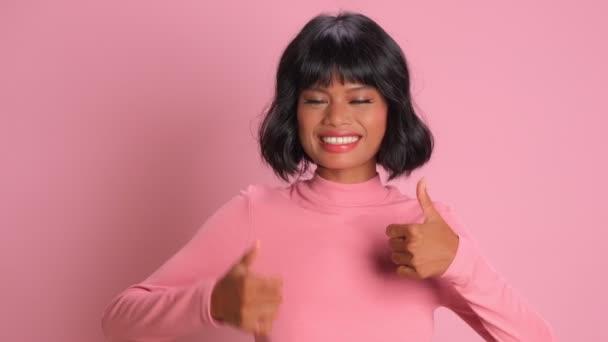 Šťastné radostné krásné smíšené rasy žena udržuje oba palce nahoru přes růžovou stěnu