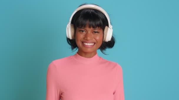 Fiatal vegyes fajú nő mosolyog széles körben hallgat zenét fülhallgató felett kék fal