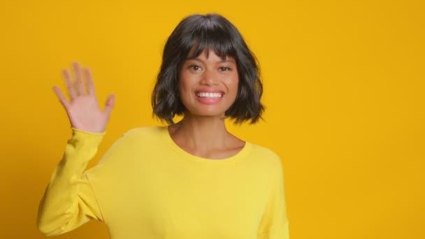 Freundliche junge Frau macht Hallo-Geste vor gelbem Hintergrund