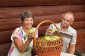 Šťastný pár s letošní bohatou sklizeň. Šťastný starší pár s košíkem hrušek dřevěné zdi domu