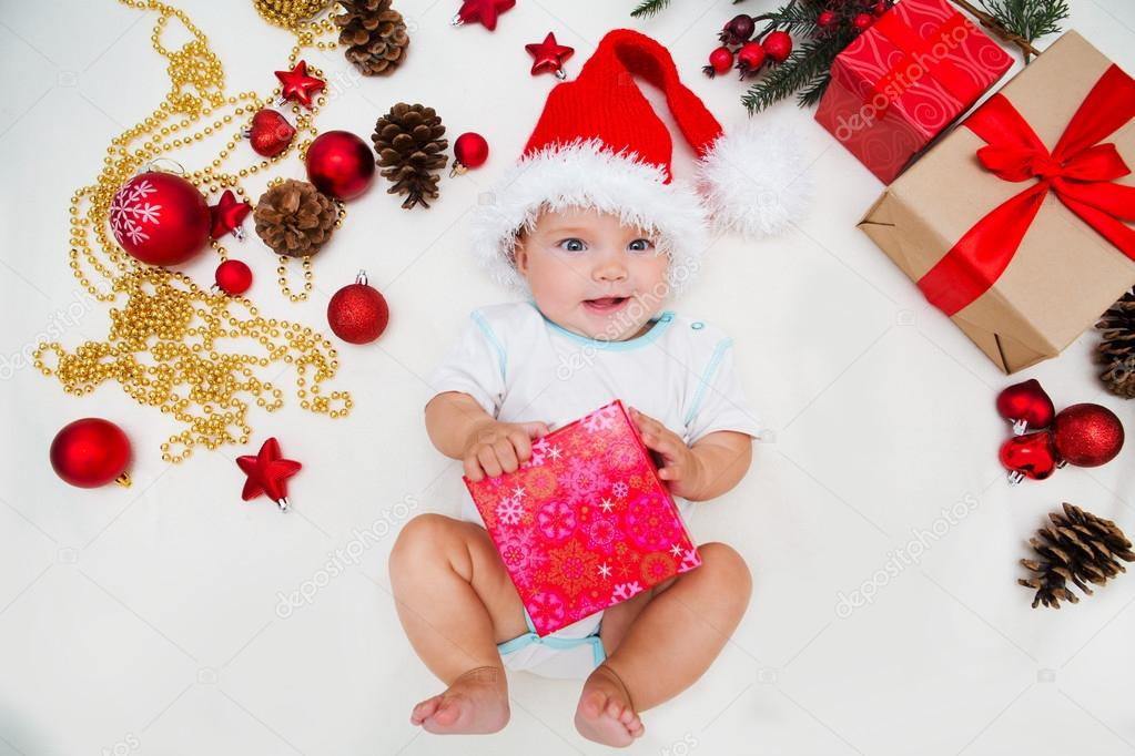 Baby first christmas. Beautiful little baby celebrates Christmas. New  Year s holidays. Baby with santa hat with gift– stock image 86da42d4fa80