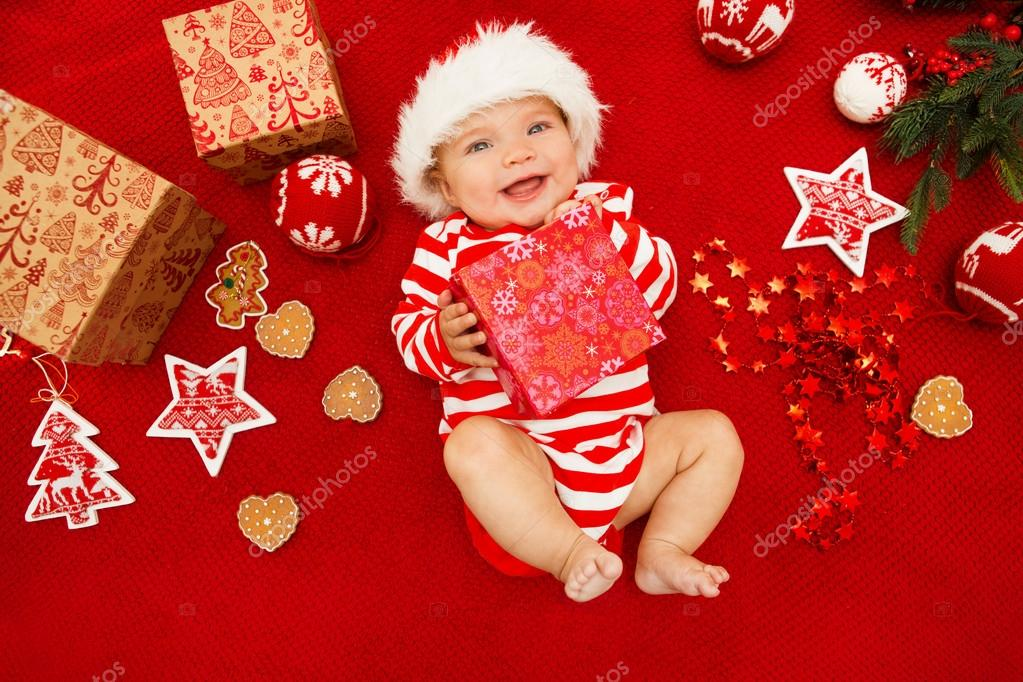 Baby first christmas. Beautiful little baby celebrates Christmas. New  Year s holidays. Baby with santa hat with gift. Santa baby.– stock image d3b040fd0de1