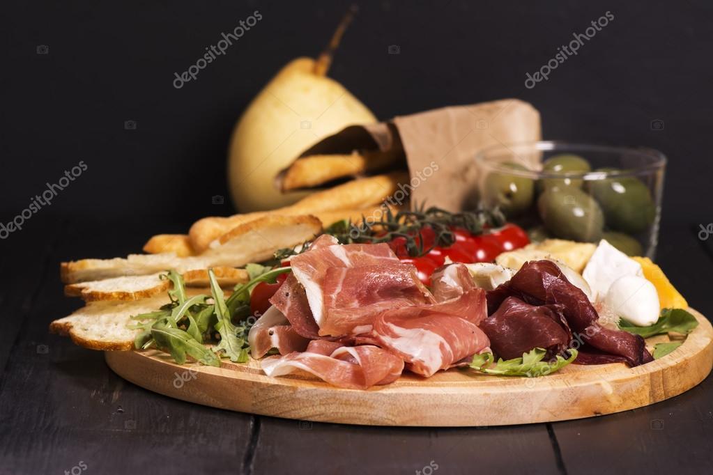 verschillende soorten italiaanse hapjes: ham, kaas, grissini