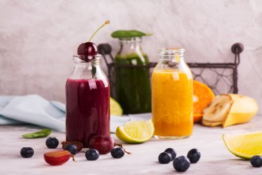Green, yellow and purple smoothies over stone table