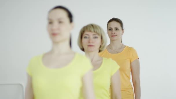 fitness, sport, vzdělávání a životním stylu koncept - skupina usmívající se žen, táhnoucí se v tělocvičně