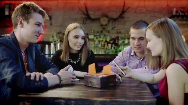 Společnost mladých lidí se dívá na něco v mobil, posezení v baru